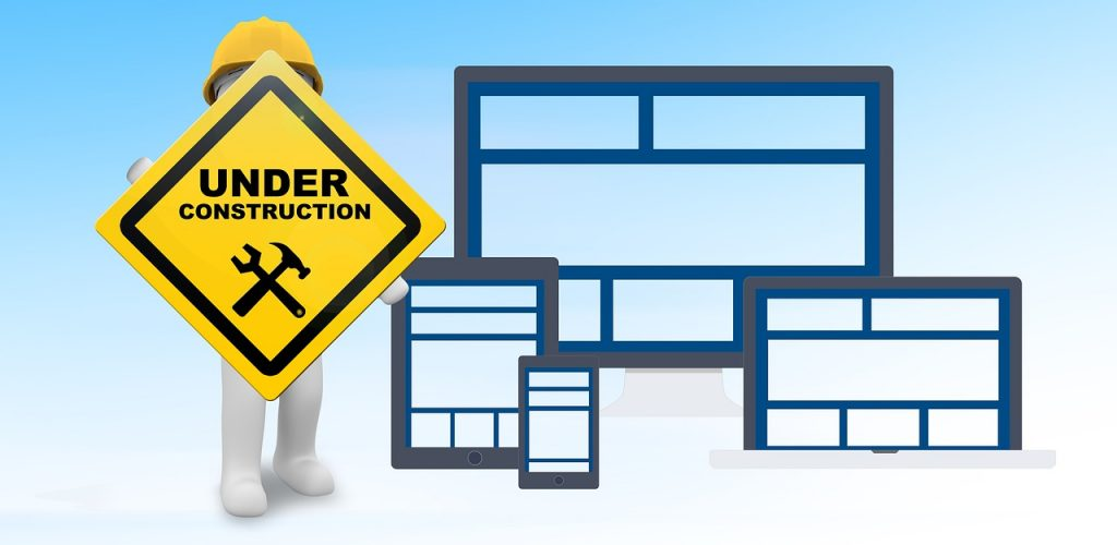 """The """"Under Construction"""" yellow sign beside website redesign mockups."""